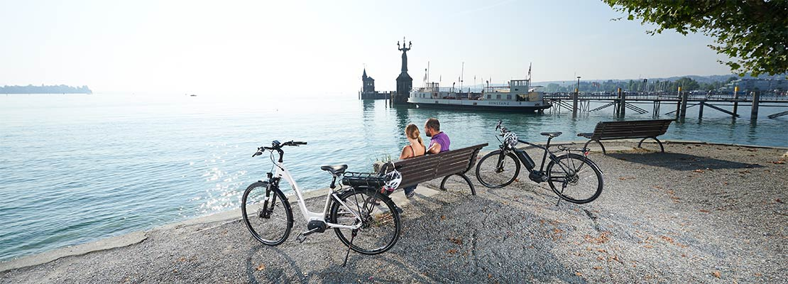 Two cyclist are making a rest on a park bench at the harbour of Konstanz.